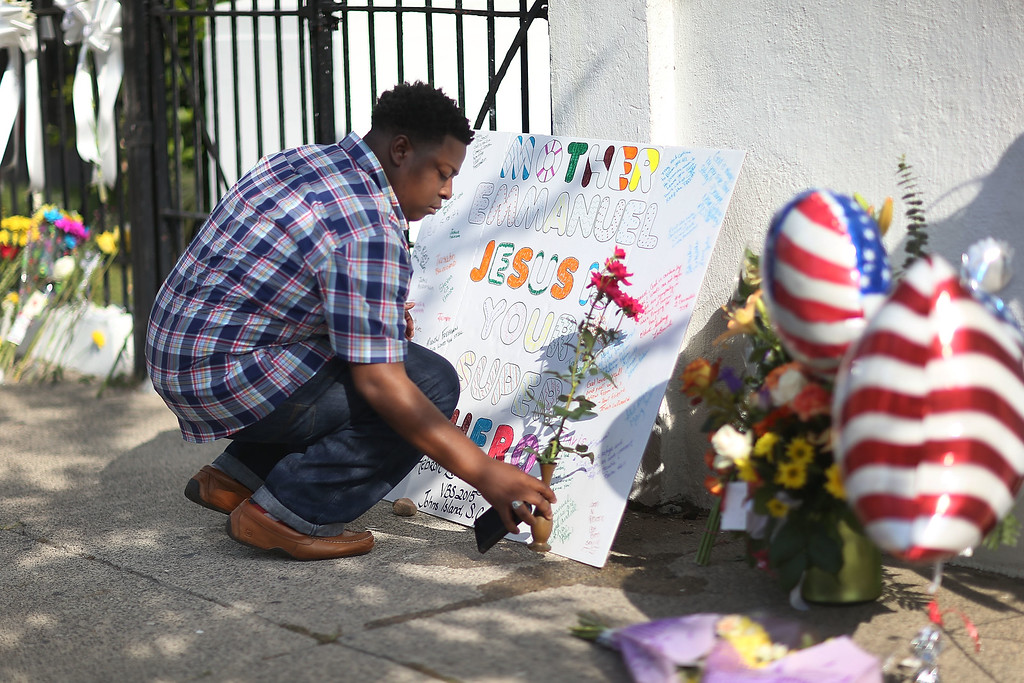 . Jermaine Jenkins pays his respects in front of Emanuel African Methodist Episcopal Church after a mass shooting at the church that killed nine people of June 19, 2015. A 21-year-old white gunman is suspected of killing nine people during a prayer meeting in the church, which is one of the nation\'s oldest black churches in Charleston. (Photo by Joe Raedle/Getty Images)