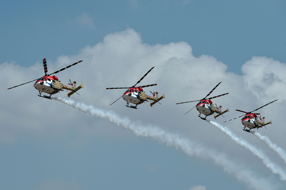 Description of . The Indian Air Force Sarang aerobatics team perform in their HAL Dhruv helicopters during Aero India 2013 at the Yelahanka Air Force station in Bangalore on February 6, 2013. India, the world's leading importer of weaponry, opened one of Asia's biggest aviation trade shows Wednesday with Western suppliers eyeing lucrative deals and a Chinese delegation attending for the first time.  Manjunath Kiran/AFP/Getty Images