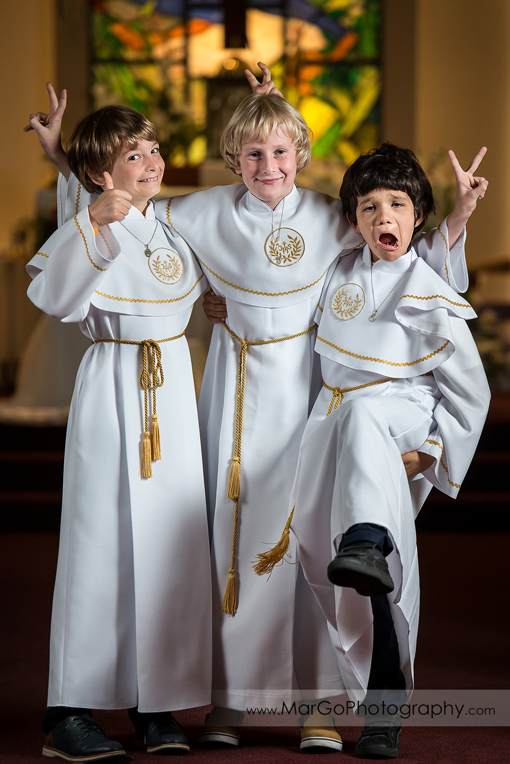 three first communion boys in white albs standing in San Jose church middle aisle