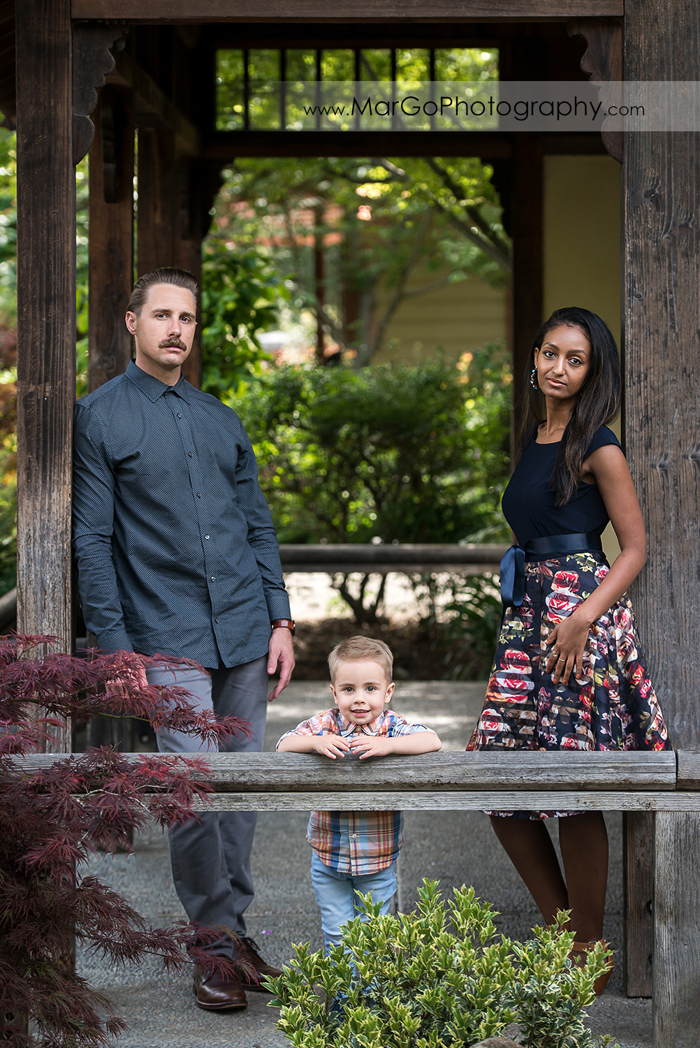 family of 3 under wooden structure in Shinn Historical Park and Arboretum in Fremont