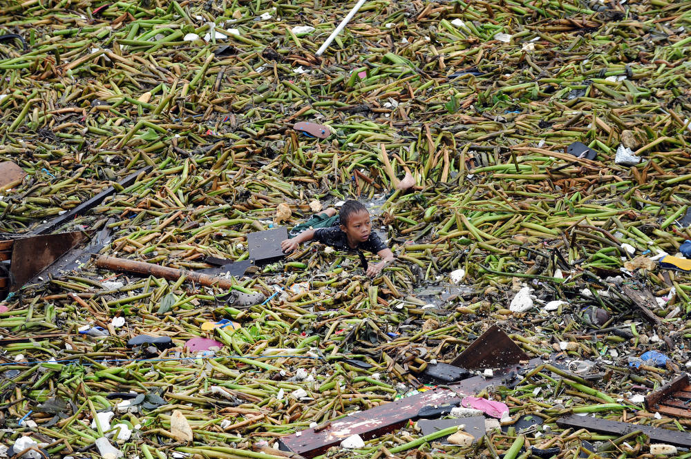 Description of . A boy swims amongst the debris as he tries to salvage belongings from destroyed homes hit after two barges smashed into an informal settler area in Manila on July 30, 2012, when strong winds and rains due to Tropical Storm Saola hit the capital.  At least one person was killed and millions were left without power on July 30, as Tropical Storm Saola brought heavy rains to large parts of the Philippines, the government said.   AFP PHOTO / TED  ALJIBE/AFP/Getty Images