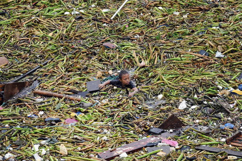 . A boy swims amongst the debris as he tries to salvage belongings from destroyed homes hit after two barges smashed into an informal settler area in Manila on July 30, 2012, when strong winds and rains due to Tropical Storm Saola hit the capital.  At least one person was killed and millions were left without power on July 30, as Tropical Storm Saola brought heavy rains to large parts of the Philippines, the government said.   AFP PHOTO / TED  ALJIBE/AFP/Getty Images