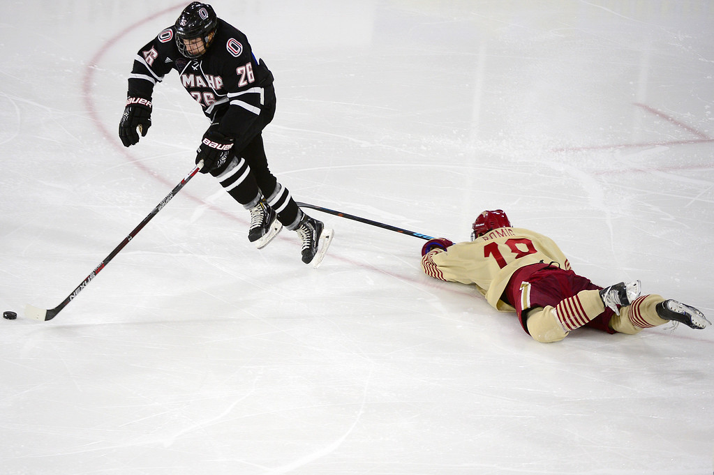 . Nebraska-Omaha Mavericks forward Steven Spinner (26) breaks away from Denver Pioneers forward Emil Romig (18) during the second period at Magness Arena on March 4, 2016 in Denver, Colorado. (Photo by Brent Lewis/The Denver Post)