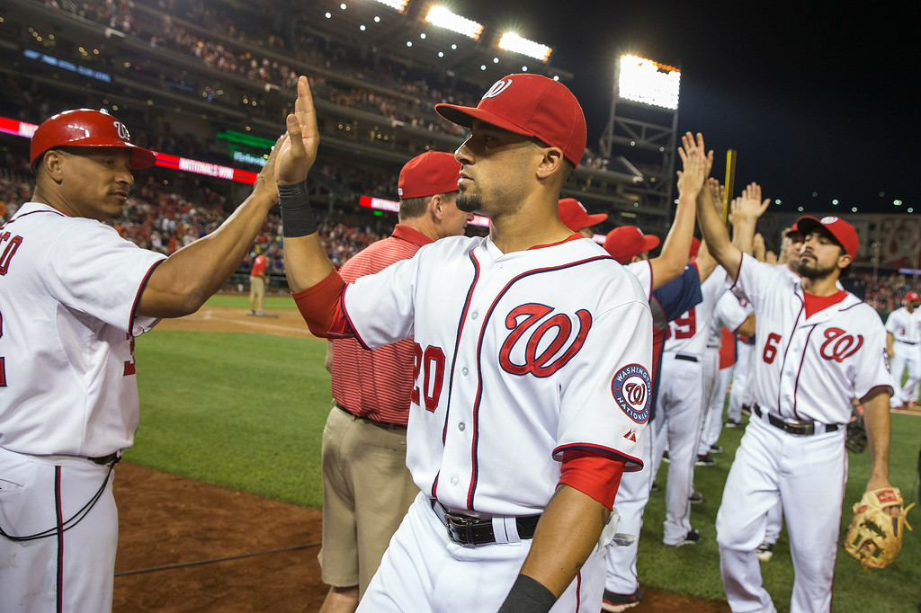 . Washington Nationals Ian Desmond is congratulated by first base coach Tony Tarasco, left, after defeating the Colorado Rockies in a baseball game 7-3 at Nationals Park, on Monday, June 30, 2014, in Washington. (AP Photo/ Evan Vucci)