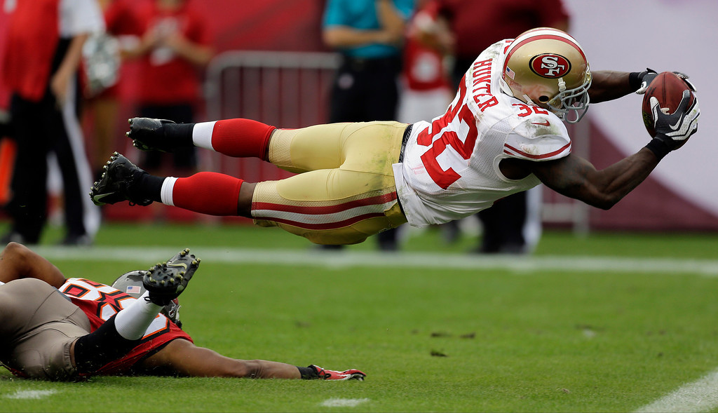 . San Francisco 49ers\' Kendall Hunter (32) dives into the end zone to score after picking up a fumble by Tampa Bay Buccaneers\' Russell Shepard during the fourth quarter of an NFL football game Sunday, Dec. 15, 2013, in Tampa, Fla. (AP Photo/Chris O\'Meara)