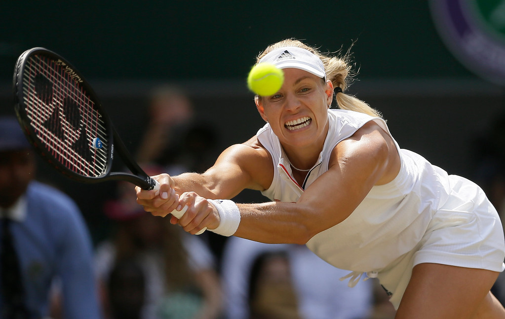 . Germany\'s Angelique Kerber returns the ball to Latvia\'s Jelena Ostapenko during their women\'s singles semifinals match at the Wimbledon Tennis Championships, in London, Thursday July 12, 2018. (AP Photo/Tim Ireland)