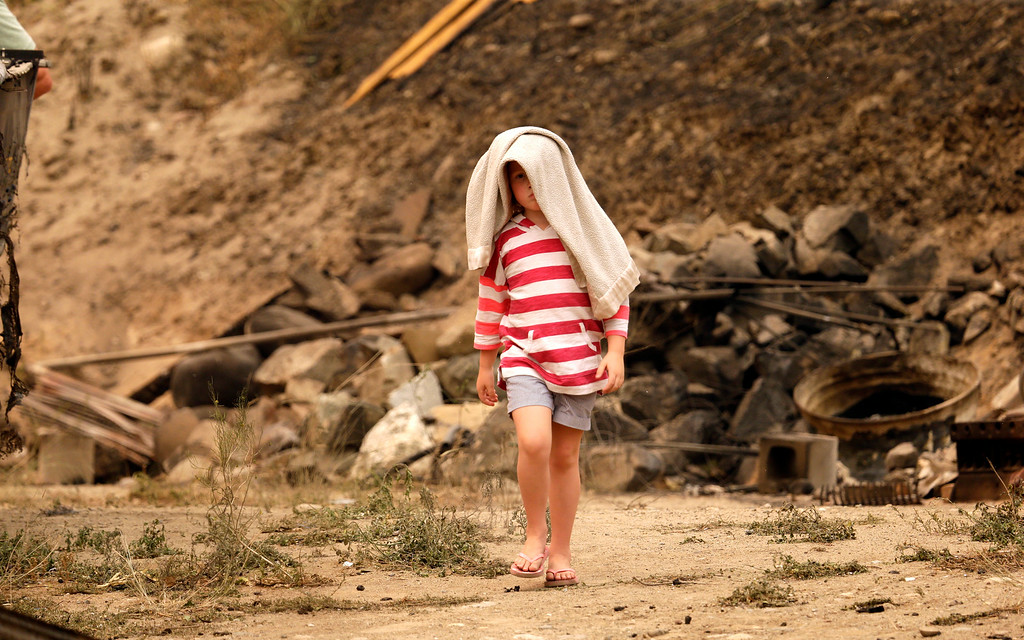 . Avery Harrison, 5, shrouds herself in her blanket as she walks away from the rubble of her family\'s home, destroyed in a wildfire the night before, while visiting the site Friday, July 18, 2014, in Pateros, Wash. A fire racing through rural north-central Washington destroyed about 100 homes, leaving behind smoldering rubble, solitary brick chimneys and burned-out automobiles as it blackened hundreds of square miles. Friday\'s dawn revealed dramatic devastation, with the Okanagan County town of Pateros, home to 650 people, hit especially hard. (AP Photo/Elaine Thompson)