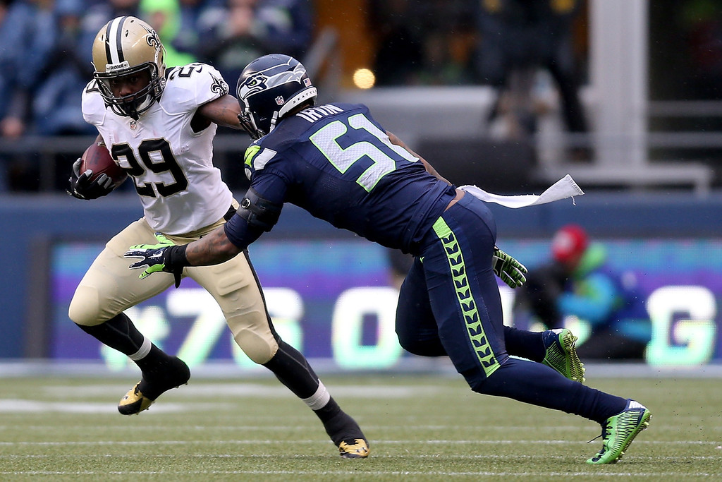 . SEATTLE, WA - JANUARY 11:  Running back Khiry Robinson #29 of the New Orleans Saints runs the ball against outside linebacker Bruce Irvin #51 of the Seattle Seahawks in the first half during the NFC Divisional Playoff Game at CenturyLink Field on January 11, 2014 in Seattle, Washington.  (Photo by Jeff Gross/Getty Images)