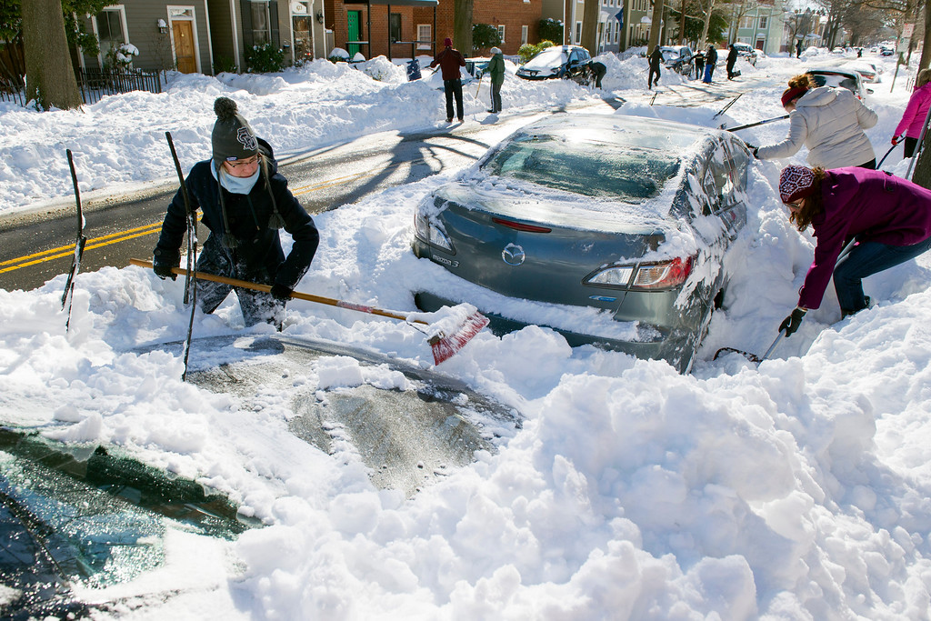 . Rhianna McCarte, 30,  joins her neighbors to dig out their cars in Alexandria, Va., Sunday, Jan. 24, 2016. Millions of Americans were preparing to dig themselves out Sunday after a mammoth blizzard with hurricane-force winds and record-setting snowfall brought much of the East Coast to an icy standstill. (AP Photo/Cliff Owen)