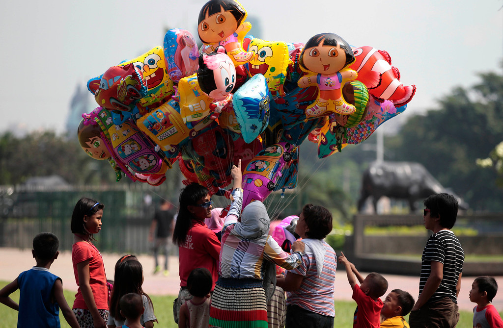 . Filipino Muslims buy balloons during Eid al-Fitr, marking the end of the holy month of Ramadan, at Manila\'s Rizal Park, Philippines Thursday, Aug. 8, 2013. (AP Photo/Aaron Favila)