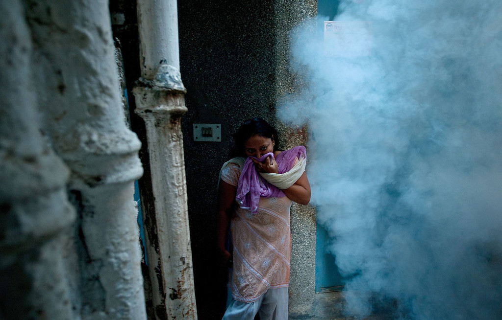 . An Indian woman covers her face from smoke after a municipal health worker fumigated against mosquitoes at a neighborhood in New Delhi on October 3, 2013. Dengue fever is a mosquito-borne disease with no known cure or vaccination that strikes fear into the citizens of New Delhi when it arrives with the monsoon rains -- just as the scorching heat of the summer is subsiding.  MANAN VATSYAYANA/AFP/Getty Images