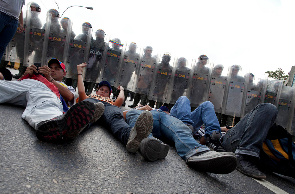 . Opposition supporters and students lie on the ground in front of riot police blocking a highway in the Altamira neighborhood of Caracas, Venezuela, Monday, April 15, 2013.  The opposition is protesting the official results in Venezuela\'s disputed Sunday presidential election.  Opposition presidential candidate Henrique Capriles has challenged his narrow loss to Nicolas Maduro and is demanding a recount. (AP Photo/Ramon Espinosa)
