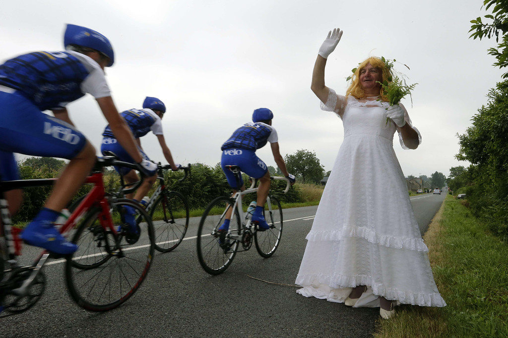 . A man dressed as a bride waves to amateurs cyclists along the road near Fougères before the start of the 218 km twelfth stage of the 100th edition of the Tour de France cycling race on July 11, 2013 between Fougères and Tours, northwestern France.  JOEL SAGET/AFP/Getty Images