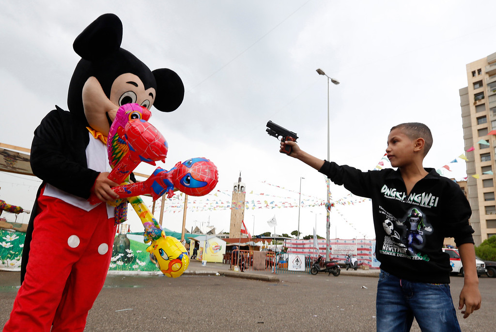 . A Syrian refugee boy points a plastic toy pistol at a man in a Mickey Mouse costume on the first day of Eid al-Adha at a park in Beirut October 26, 2012. Muslims around the world celebrate Eid al-Adha, marking the end of the haj, by slaughtering sheep, goats, cows and camels to commemorate Prophet Abraham\'s willingness to sacrifice his son Ismail on God\'s command. REUTERS/Jamal Saidi