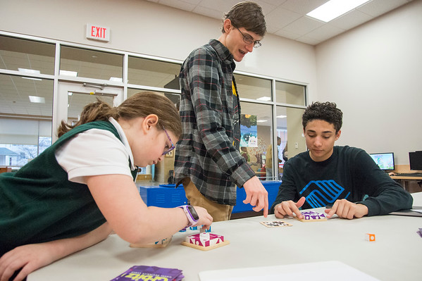 01/13/20 Wesley Bunnell | StaffrrAngel Rodriguez , age 8, works on a Q-Bitz game puzzle in the Bristol Boys and Girls Club on Monday afternoon as co-leaders of the tech program Nathan Benham and Josias Reynoso discuss how to build a robot to compete in the game.