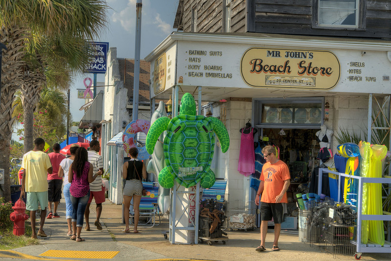 People walk along Center Street and Mr. John's Beach Store, one of the oldest businesses in town, in Folly Beach, SC on Sunday, September 8, 2013. Copyright 2013 Jason Barnette