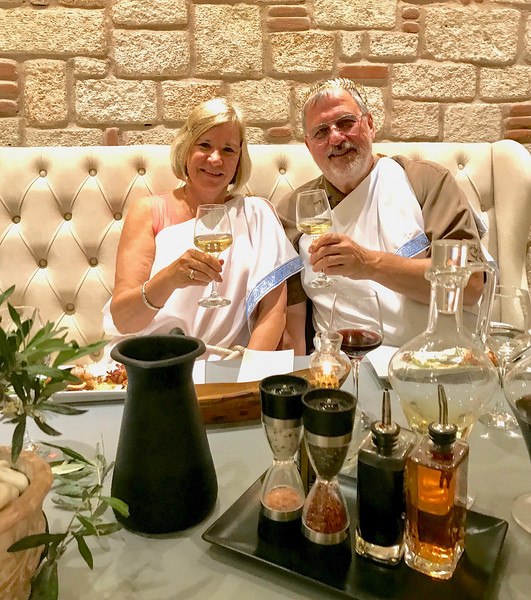 two boomers in togas with a glass of wine