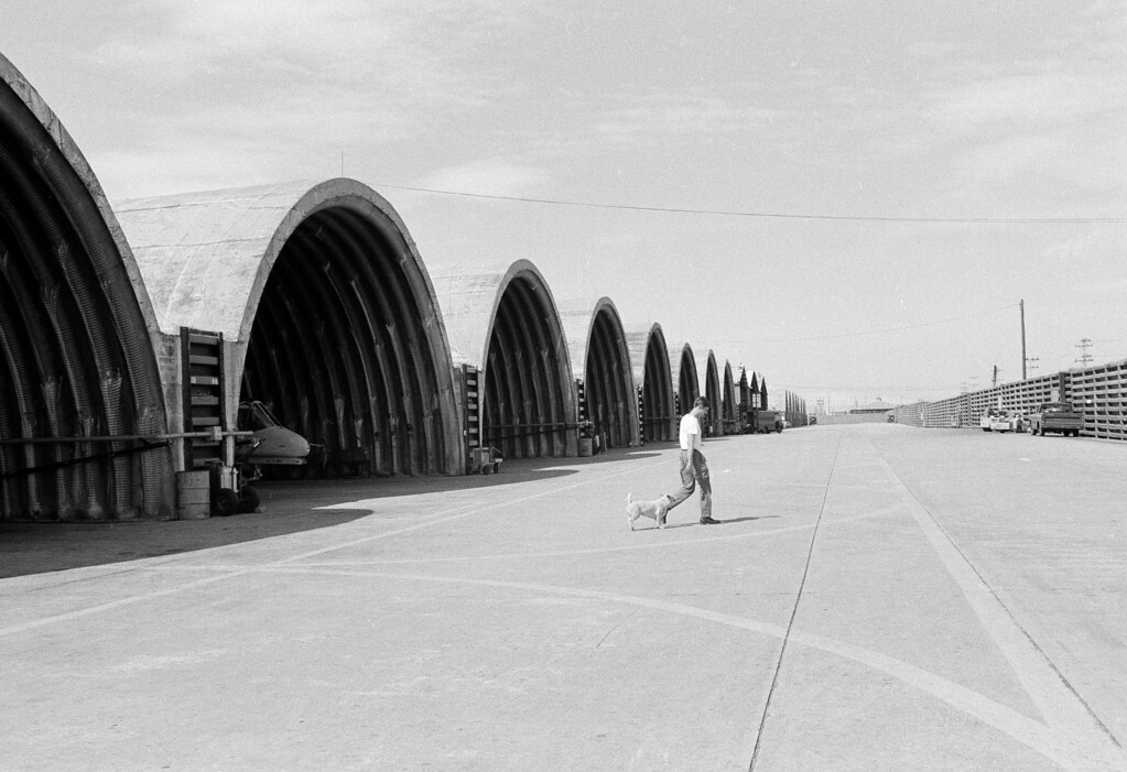 . A U.S. airman, his pet dog following behind him, walks past the quiet and deserted hangars at Da Nang Air Base, Jan. 29, 1973.  Four thousand Americans here are preparing to go home, but this airman\'s dog will not be allowed to go home with him.  (AP Photo/Dang Van Phuoc)