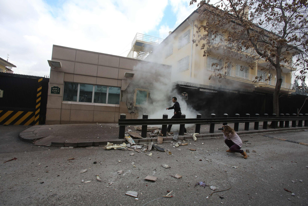 . A security officer runs after an explosion at the entrance of the U.S. embassy in Ankara February 1, 2013. A suicide bomber killed a Turkish security guard (not in picture) at the U.S. embassy in Ankara on Friday, blowing the door off a side entrance and sending smoke and debris flying into the street.  REUTERS/Yavuz Ozden/Milliyet Daily Newspaper