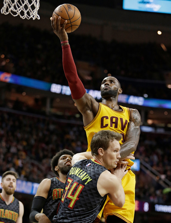 . Cleveland Cavaliers\' LeBron James (23) drives to the basket as Atlanta Hawks\' Mike Dunleavy (34) is called for a foul in the second half of an NBA basketball game, Friday, April 7, 2017, in Cleveland. (AP Photo/Tony Dejak)