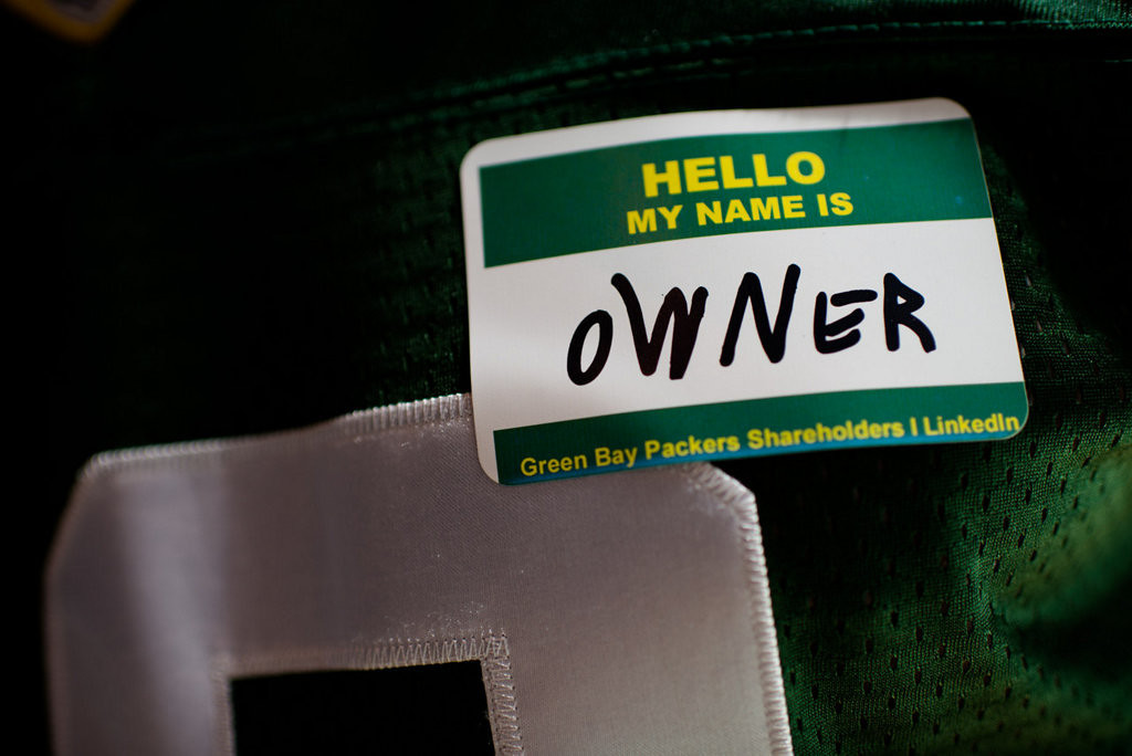 """. Jim Spath of Wisconsin Rapids, Wis.  wears an \""""owner\"""" name tag during the Packers annual shareholders meeting at Lambeau Field. (AP Photo/The Green Bay Press-Gazette, Lukas Keapproth)"""