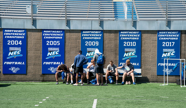 08/29/19 Wesley Bunnell | Staff CCSU's football practice on Thursday August 29, 2019. Players sit after practice with several NEC champion banners behind them.