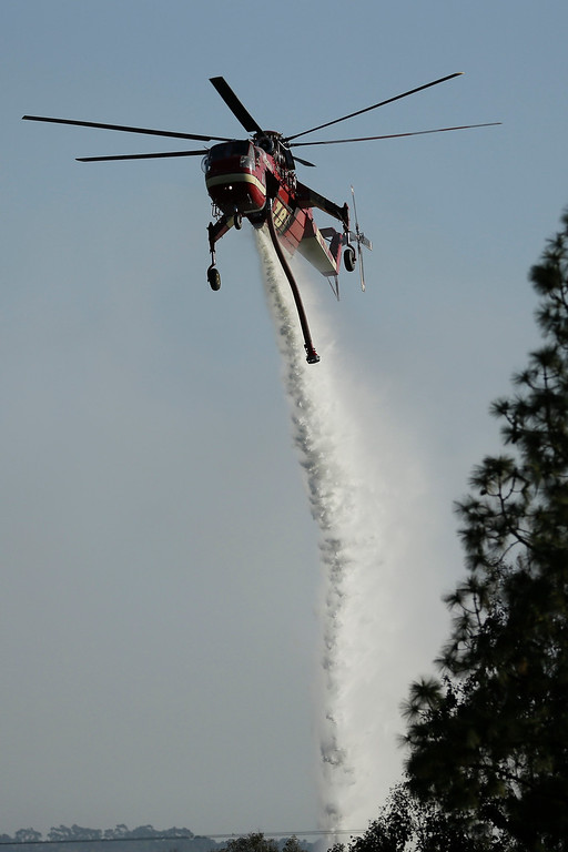 . A helicopter drops water on a wildfire in the Rancho Santa Fe neighborhood Tuesday, May 13, 2014, in San Diego. Wildfires pushed by gusty winds chewed through canyons parched by California\'s drought, prompting evacuation orders for more than 20,000 homes on the outskirts of San Diego and another 1,200 homes and businesses in Santa Barbara County 250 miles to the north. (AP Photo)