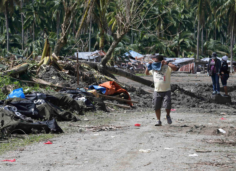 . A resident covers his nose as he walks past typhoon Bopha\'s victims which are left unattended at New Bataan township, Compostela Valley in southern Philippines Saturday Dec. 8, 2012. Search and rescue operations following typhoon Bopha that killed nearly 600 people in the southern Philippines have been hampered in part because many residents of this ravaged farming community are too stunned to assist recovery efforts, an official said Saturday. (AP Photo/Bullit Marquez)