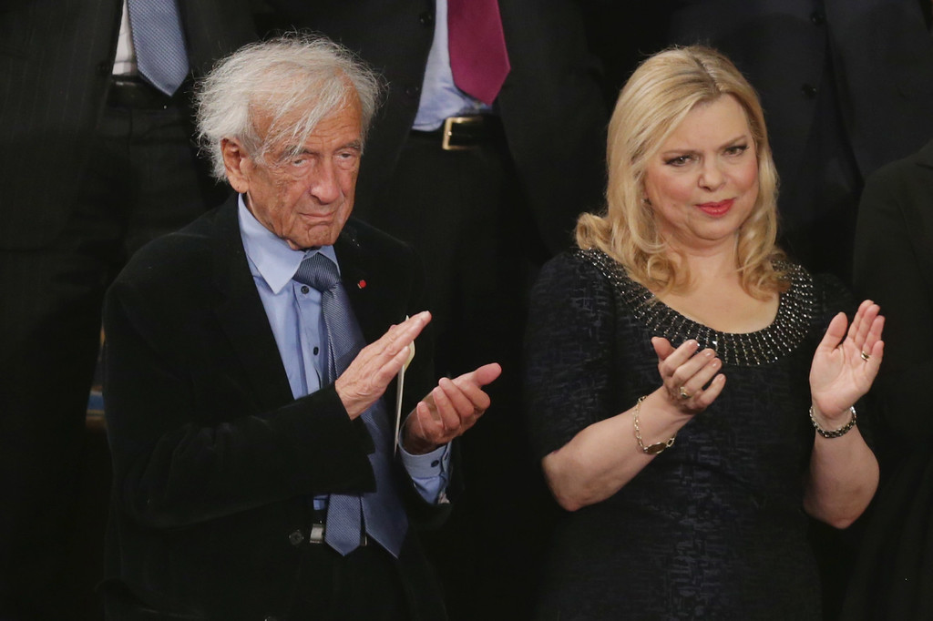 . Professor, political activist and Holocaust survivor Elie Wiesel (L) and Israeli Prime Minister Benjamin Netanyahu\'s wife Sara Netanyahu applaud for the prime minister during his address to a joint meeting of Congress in the House chamber at the U.S. Capitol March 3, 2015 in Washington, DC. At the risk of further straining the relationship between Israel and the Obama Administration, Netanyahu warned members of Congress against what he considers an ill-advised nuclear deal with Iran.  (Photo by Chip Somodevilla/Getty Images)
