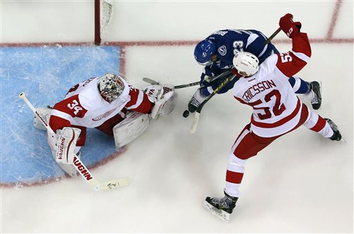 . Detroit Red Wings goalie Petr Mrazek (34), of the Czech Republic, makes a save on a shot by Tampa Bay Lightning right wing J.T. Brown (23) as Red Wings\' Jonathan Ericsson (52) defends during the second period of Game 1 of an NHL hockey first-round playoff series Thursday, April 16, 2015, in Tampa, Fla. Detroit won 3-2. (AP Photo/Chris O\'Meara)