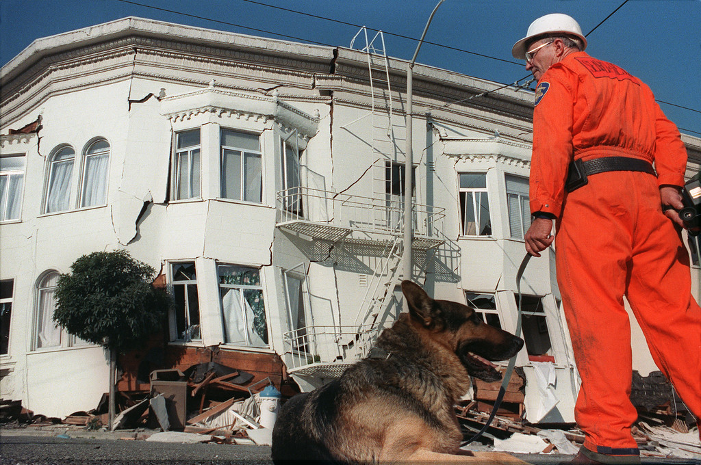 . A rescuer looks at a collapsed house, on October 18, 1989, in the Marina District of San Francisco, one of the areas hardest hit in the city by a 6.9 earthquake on October 17, 1989. (ADAM TEITELBAUM/AFP/Getty Images)