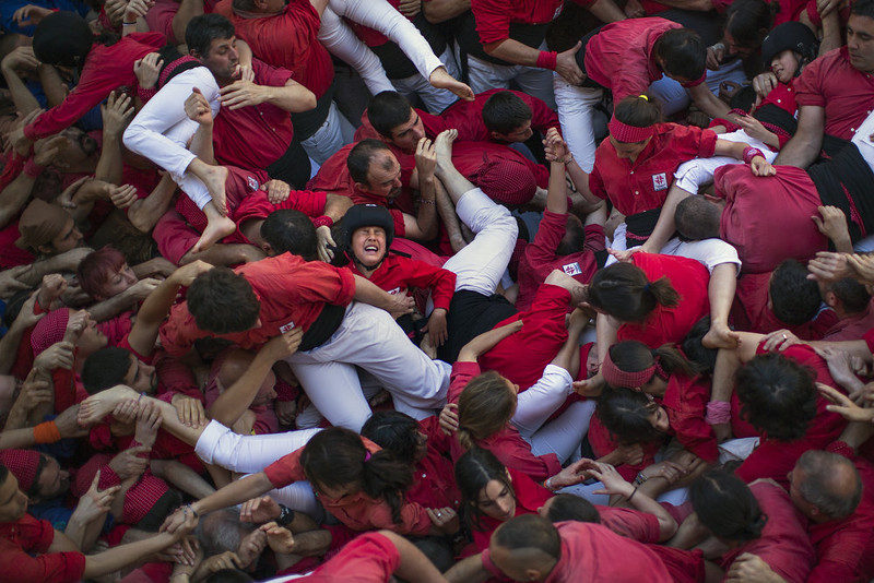 ". Members of the Castellers of Barcelona crowd together after the collapse of their  ""castell\"" or human tower in the Barcelona neighborhood of Gracia, Catalonia, Spain on Sunday May 19, 2013. A \""castell\"" is a human tower traditionally built during festivals in many places in Catalonia. At these festivals, several \""colles\"" or teams compete to build the most impressive towers they can. A few participants were slightly wounded after the collapse of the human tower and were evacuated to the hospital. (AP Photo/Emilio Morenatti)"