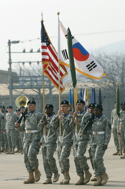 """. Soldiers of the U.S. Army 23rd chemical battalion carry a U.S. and South Koream flag during a ceremony to recognize the battalion\'s official return to the 2nd Infantry Division based in South Korea at Camp Stanley in Uijeongbu, north of Seoul, Thursday, April 4, 2013. The 23rd chemical battalion left South Korea in 2004 and returned with some 350 soldiers in Jan. 2013. The battalion will provide nuclear, biological and chemical detection, equipment decontamination and consequence management assistance to support the U.S. and South Korean military forces. North Korea warned Thursday that its military has been cleared to attack the U.S. using \""""smaller, lighter and diversified\"""" nuclear weapons, while the U.S. said it will strengthen regional protection by deploying a missile defense system to Guam. (AP Photo/Lee Jin-man)"""