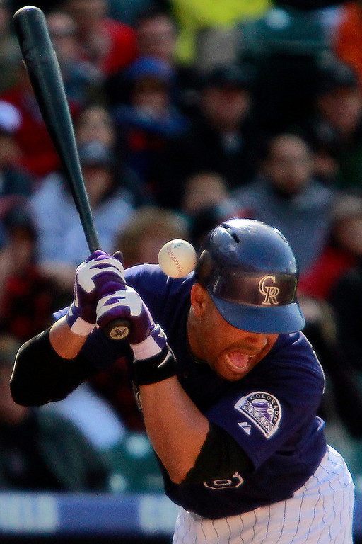 . Colorado Rockies\' Yorvit Torrealba (8) is hit by a pitch from Atlanta Braves\' Cory Gearrin during the 1-th inning of a baseball game, Wednesday, April 24, 2013, in Denver. The Rockies won 6-5 in the 12th inning. (AP Photo/Barry Gutierrez)