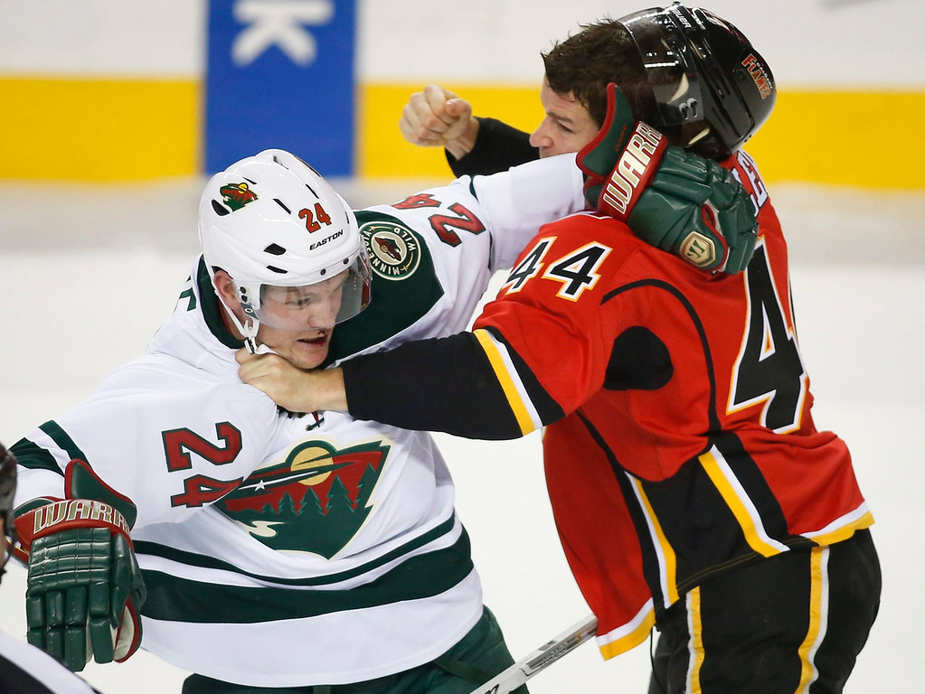 . Minnesota Wild\'s Matt Cooke, left, fights with Calgary Flames\' Chris Butler during first-period NHL hockey game action in Calgary, Alberta, Saturday, Feb. 1, 2014. (AP Photo/The Canadian Press, Jeff McIntosh)