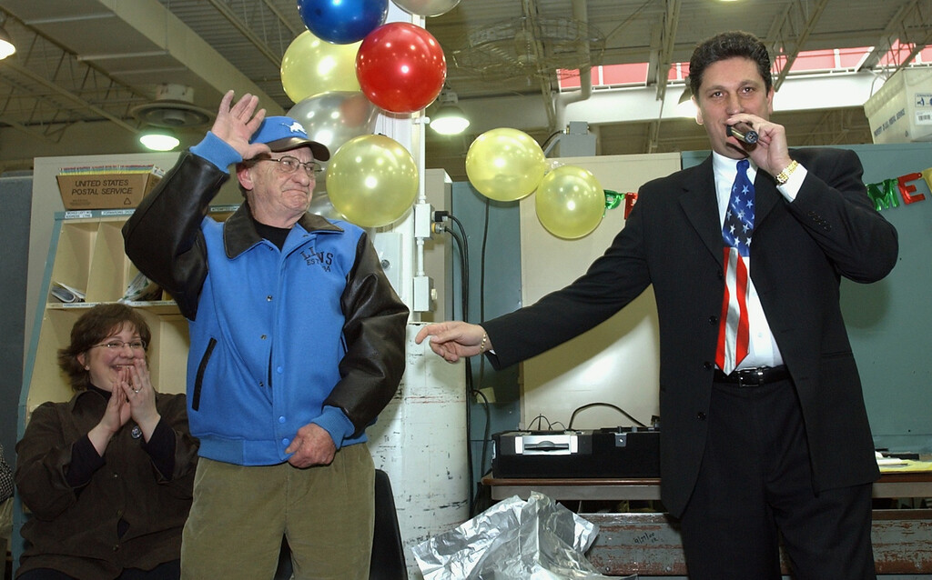 . (right)Joe Spiteri, branch manager, leads the ceremonies for Richard Drennan\'s retirement party from the post office at the West Bloomfield Post Office Wednesday. One of the gifts Drennan received from fellow employees was a Detroit Lions jacket.