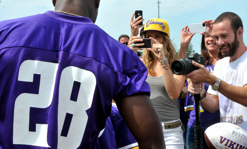 . Everywhere he turns, Vikings running back Adrian Peterson faces, with good grace, throngs armed with various implements of digital recording, from the cheapest cell phone camera to  complex and expensive professional cameras, in this instance during his morning workout in  Mankato on Tuesday, Aug. 6, 2013.   (Pioneer Press: John Doman)
