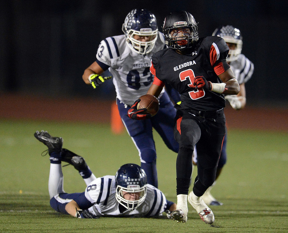 . Glendora\'s TyRell Evans (3) runs for a first down past the diving Los Osos\' Tyler Lyon (8) in the first half of a prep football game at Citrus College in Glendora, Calif., on Thursday, Oct. 31, 2013.    (Keith Birmingham Pasadena Star-News)