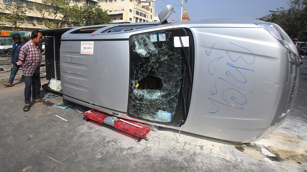 . An overturned police van lies on a road after clashes between police and anti-government demonstrators in Bangkok, Thailand, Tuesday, Feb. 18, 2014. (AP Photo/Sakchai Lalit)