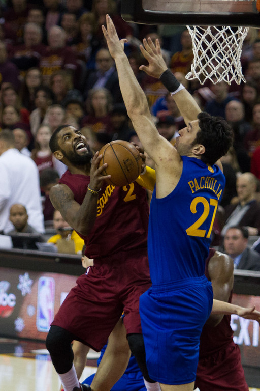 . Kyrie Irving (2) of the Cleveland Cavaliers goes up for a lay up against the Warriors\' Zaza Pachulia (27) during an NBA game at the Quicken Loans Arena on Christmas day.  The Cavs defeated the Warriors 109-108.  Michael Johnson - The News Herald