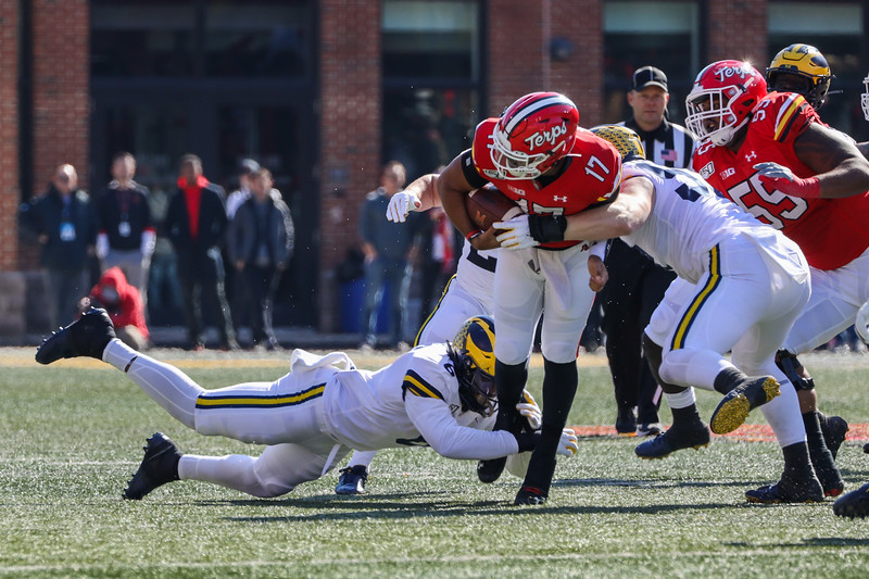 Maryland QB Josh Jackson is tackled by Michigan defenders.
