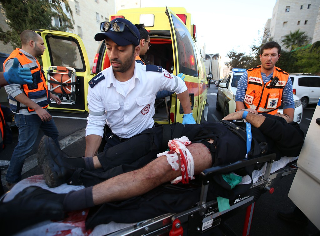 . An Israeli man that was injured  in an attack, by two Palestinians on Israeli worshippers at a synagogue, is taken to an ambulance by emergency personnel in the ultra-Orthodox Har Nof neighborhood in Jerusalem on November 18, 2014. AFP PHOTO / MIRI TSACHIE      MIRI TSACHIE/AFP/Getty Images