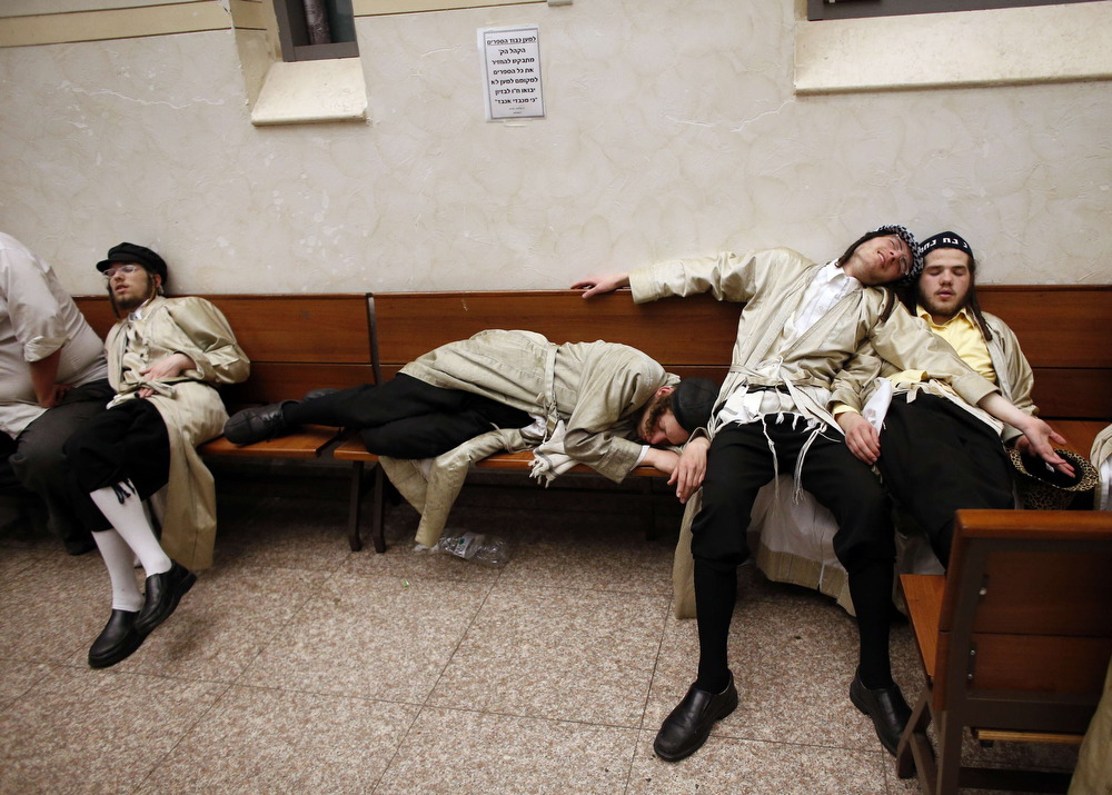 . Ultra-Orthodox Jewish men celebrate the Purim holiday in the ultra-orthodox Mea Shearim neighborhood in Jerusalem on March 17, 2014. The carnival-like Purim holiday is celebrated with parades and costume parties and drinking wine to commemorate the deliverance of the Jewish people from a plot to exterminate them in the ancient Persian empire 2,500 years ago, as recorded in the Biblical Book of Esther. (THOMAS COEX/AFP/Getty Images)