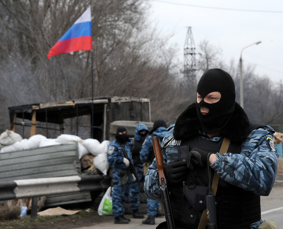 . Armed masked men who call  themselves members of Ukraine\'s disbanded elite Berkut riot police force stand at their checkpoint under a Russian flag on a highway that connect Black Sea Crimea  peninsula to mainland Ukraine near the city of Armyansk, on February 28, 2014.  AFP PHOTO / VIKTOR DRACHEV/AFP/Getty Images