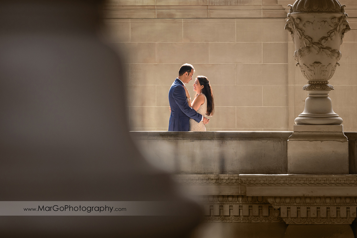 woman in beige dress and man in navy blue suit looking at each other on the fourth floor balcony of San Francisco City Hall