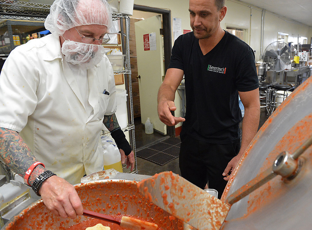 . David Saverino, right, and Ron Trace the head chef for Da\'Kine Foods, check the consistency of tomatoes being prepared in a mixer during the cooking and bottling process at Da\'Kine. Following the successful launch of Saverino\'s Italian Deli and Market in Redlands nearly two years ago, David Saverino is bottling the flavor of his business with the introduction of four separate sauces. In addition to selling the sauces at his deli, Saverino hopes to see his product on the shelves of local markets. (Photo by Rick Sforza/Redlands Daily Facts)