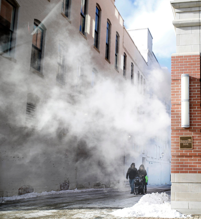 . Pedestrians walk through steam from the Berkshire Bank building on North Street during a frigid winter day Wednesday, Dec. 27, 2017, in Pittsfield, Mass. (Stephanie Zollshan/The Berkshire Eagle via AP)