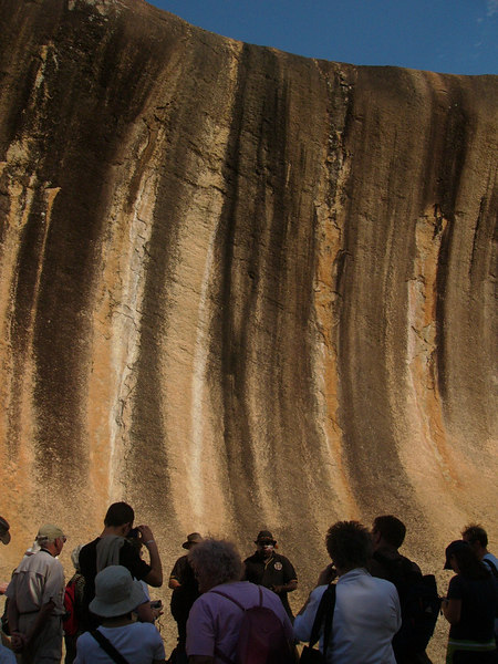 """20060421_1817 <a href=""""http://en.wikipedia.org/wiki/Wave_Rock"""">Wave Rock</a>. The black marks streaming from the cliff-edge are due to algae. The Aboriginals believed this represented the hair of a witch-like figure who stole children. These children are the little stars which can be seen in the Milky Way. Occasionally one of those stars fall out of the sky, and is seen as a 'shooting star (meteor)'."""