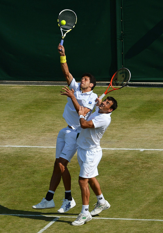 . LONDON, ENGLAND - JULY 04:  Marcelo Melo of Brazil and Ivan Dodig of Croatia collide when attempting to smash the ball during the Gentlemen�s Doubles semi final match against Radek Stepanek of Czech Republic and Leander Paes of India on day ten of the Wimbledon Lawn Tennis Championships at the All England Lawn Tennis and Croquet Club on July 4, 2013 in London, England.  (Photo by Mike Hewitt/Getty Images)