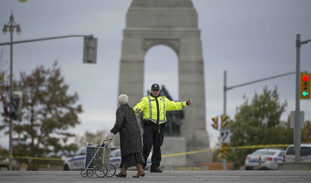 . A police officer directs traffic near the National War Memorial in Ottawa, Canada on October 22, 2014.   AFP PHOTO / Lars Hagberg/AFP/Getty Images
